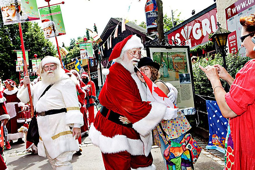 A group of Santas interact with visitors in the Dyrehavsbakken amusement park, north of Copenhagen, Denmark, Monday, July 19, 2010 for the World Santa Claus Congress, which has been held 52 times now at the amusement park. Every summer, Santas from the entire world get together at Bakken to spread some Christmas cheer, have fun, and enjoy a get-together. (AP Photo/Polfoto, Nanna Kreutzmann)