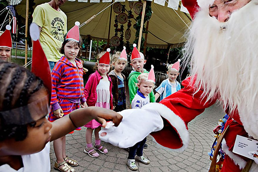 A  Santa interacts with children at the Dyrehavsbakken amusement park, north of Copenhagen, Denmark, Monday, July 19, 2010. Many have gathered for the World Santa Claus Congress, which has been held 52 times now at the amusement park. (AP Photo/Polfoto, Nanna Kreutzmann)