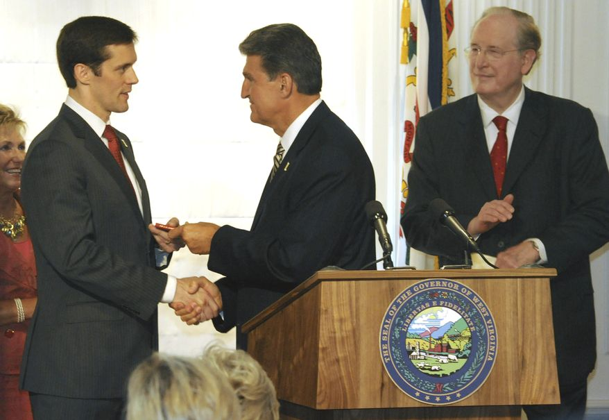** FILE ** West Virginia Gov. Joe Manchin III (center) hands Carte Goodwin (left) a copy of the U.S. Constitution during a news conference at the Capitol in Charleston, W.Va., on Friday, July 16, 2010. Mr. Manchin named Mr. Goodwin, a member of a prominent West Virginia family, to fill temporarily the U.S. Senate seat vacated by the death of Sen. Robert C. Byrd. On Tuesday, Mr. Manchin announced his candidacy for the seat. Sen. John D. Rockefeller IV looks on at right. (AP Photo/Charleston Gazette, Lawrence Pierce)