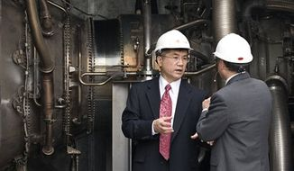 FILE - In this July 15, 2009 file photo, U.S. Secretary of Commerce Gary Locke, center, chats with an unidentified Chinese officer as he looks at a turbine inside the China Resources Golden Concord-Co-generation Plant at the Beijing Development Area in Beijing. China has overtaken the United States as the world's largest energy consumer, the International Energy Agency said Tuesday, July 20, 2010. China immediately questioned the calculation. (AP Photo/Andy Wong, File)