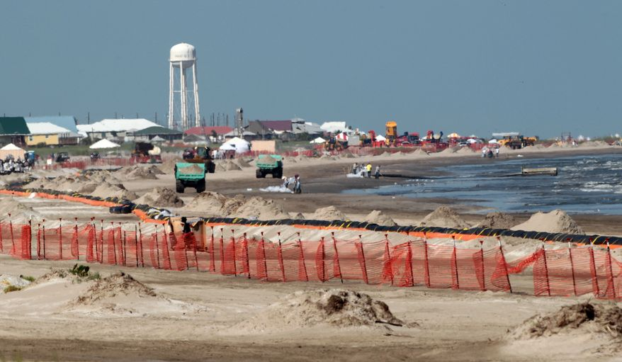 Workers clean up oil deposits from the beach on Monday, July 19, 2010, in Grand Isle, La., where petroleum from the Deepwater Horizon spill continues to wash ashore. (AP Photo/Dave Martin)