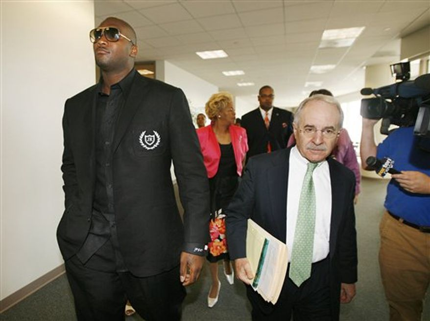 Former Oakland Raiders quarterback JaMarcus Russell, left, leaves his arraignment on a drug charge with attorney Donald Briskman Tuesday, July 20, 2010, in downtown Mobile, Ala. Russell pleaded not guilty. (AP Photo/Press-Register, Mike Kittrell)