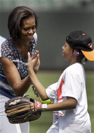 First lady Michelle Obama high-fives a player during a sport clinic with area youths and members of the Baltimore Orioles and Tampa Bay Rays baseball teams, Tuesday, July 20, 2010, at Oriole Park at Camden Yards in Baltimore. Obama was taking part in an event with Major League Baseball and the MLB Players Association that will team with the White House in the Let's Move campaign, which promotes exercise and healthy eating for America's youth. (AP Photo/Rob Carr)