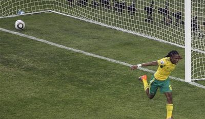 """FILE - In this Friday June 11 2010 file photo,  South Africa's Siphiwe Tshabalala celebrates after scoring the opening goal of the World Cup Soccer Tournament at the Soccer City Stadium in Johannesburg. South Africa's soccer association says the shoes Siphiwe Tshabalala used to score the first goal at the World Cup will become a """"historic monument"""" to South African soccer. SAFA chief executive Leslie Sedibe told a parliamentary committee on Tuesday, July 20, 2010, that the shoes will go on display at SAFA headquarters in Johannesburg. (AP Photo/Marcio Sanchez, File)"""