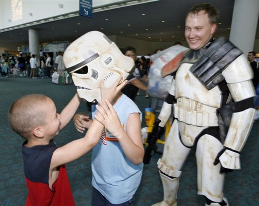 FILE - In this July 22, 1006 file photo, Andrew Ebanks, left, helps his brother Adam Ebanks, center, with a Storm Trooper helmet borrowed from Dana Gasser, right, at  Comic-Con International at the San Diego Convention Center.  (AP Photo/Denis Poroy, file)