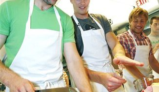 In this Thursday, July 15, 2010, photo, Minnesota Wild NHL hockey player Colton Gillies, left, gets some tips on cutting parsley from fellow player Justin Falk during a cooking class as a break during Wild hockey development camp in St. Paul, Minn. (AP Photo/Andy King)
