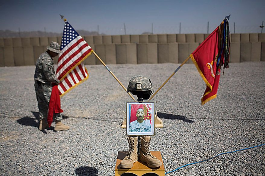 A U.S. Army soldier holds a U.S. flag next to a portrait of Pfc. Brandon King, from the 1-320th Alpha Battery, 2nd Brigade of the 101st Airborne Division, who was killed July 14 at COB Nolan, during a memorial service at Combat Outpost Terra Nova in the volatile Arghandab Valley, Kandahar, Afghanistan, Tuesday, July 20, 2010. (AP Photo/Rodrigo Abd)