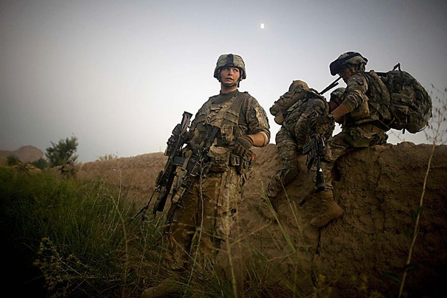 U.S. Army soldiers from the 1-320th Alpha Battery, 2nd Brigade of the 101st Airborne Division, climb over a mud wall during a patrol towards COB Nolan, in the volatile Arghandab Valley, Kandahar, Afghanistan, Tuesday, July 20, 2010. (AP Photo/Rodrigo Abd)