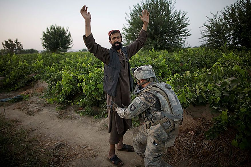 A U.S. Army soldier from the 1-320th Alpha Battery, 2nd Brigade of the 101st Airborne Division searches an Afghan villager during a foot patrol towards COB Nolan, in the volatile Arghandab Valley, Kandahar, Afghanistan, Tuesday, July 20, 2010. (AP Photo/Rodrigo Abd)