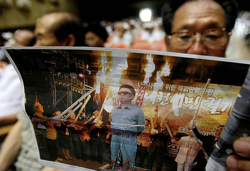 A South Korean veteran reads a leaflet with a photo of South Korean conservative activists preparing to burn a cutout of North Korean leader Kim Jong Il during a rally denouncing North Korea in Chunan South Korea, Tuesday, July 20, 2010. U.S. Defense Secretary Robert Gates arrived Monday in South Korea on a trip to underscore Washington's firm alliance with Seoul as the two nations plan military exercises in a message of deterrence to North Korea. (AP Photo/Ahn Young-joon)