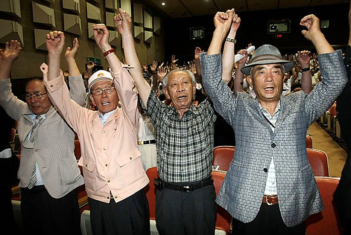 South Korean veterans cheer up during a rally denouncing North Korea in Chunan, South Korea, Tuesday, July 20, 2010. U.S. Defense Secretary Robert Gates arrived Monday in South Korea on a trip to underscore Washington's firm alliance with Seoul as the two nations plan military exercises in a message of deterrence to North Korea. (AP Photo/Ahn Young-joon)