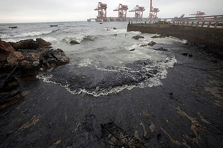 This photo released by Greenpeace shows oil washed ashore near the port of Dalian, China, on Tuesday, July 20, 2010. Crude oil started pouring into the Yellow Sea off a busy northeastern port after a pipeline exploded late last week, sparking a massive 15-hour fire. The government says the slick has spread across a 70-square-mile stretch of ocean. (AP Photo/Jiang He, Greenpeace)