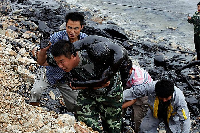 In this photo released by Greenpeace, a firefighter who was submerged in thick oil during an attempt to fix an underwater pump is brought ashore by his colleagues in Dalian,  China, on Tuesday, July 20, 2010. Crude oil started pouring into the Yellow Sea off a busy northeastern port after a pipeline exploded late last week, sparking a massive 15-hour fire. The government says the slick has spread across a 70-square-mile stretch of ocean. (AP Photo/Jiang He, Greenpeace)