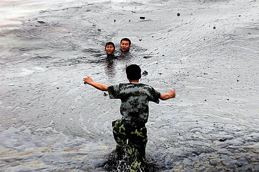 In this photo released by Greenpeace, a firefighter rush to aid his colleagues who ran into trouble amid thick oil cover as they attempted to fix an underwater pump in Dalian, China port of Dalian, China, on Tuesday, July 20, 2010. Crude oil started pouring into the Yellow Sea off a busy northeastern port after a pipeline exploded late last week, sparking a massive 15-hour fire. The government says the slick has spread across a 70-square-mile stretch of ocean. (AP Photo/Jiang He, Greenpeace)