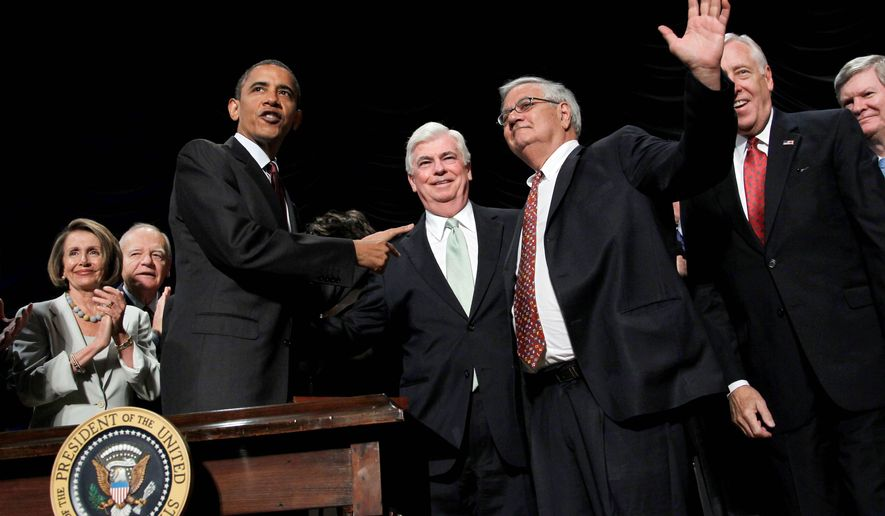 President Obama gives credit to two Democrats, Sen. Christopher J. Dodd, and Rep. Barney Frank (hand raised), after signing the Wall Street Reform and Consumer Protection Act on Wednesday. The two lawmakers chair key finance committees. At left is House Speaker Nancy Pelosi. (Associated Press)