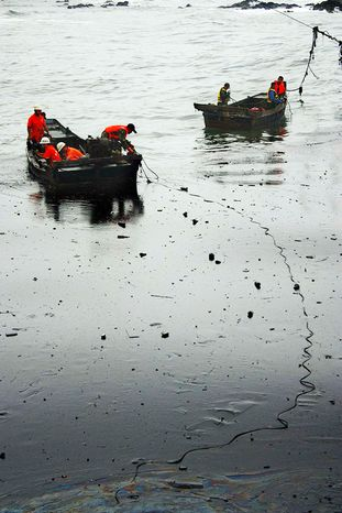 """Chinese firefighters work to clean up the oil spill near the coast of Dalian, China, on Tuesday. Crude oil began pouring into the Yellow Sea after a pipeline exploded last week, and officials say the spill poses a """"severe threat"""" to sea life and water quality. (Associated Press)"""