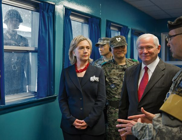 A U.N. Command soldier keeps a watchful eye on a North Korean soldier peering in through a window as U.S. Army Col. Kurt Taylor briefs Secretary of State Hillary Rodham Clinton and Defense Secretary Robert M. Gates on Wednesday. (Associated Press)