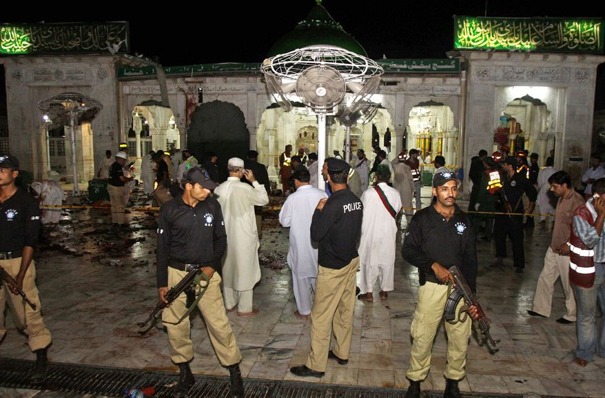 Pakistani police officers guard the area where suicide bombers attacked a sacred Muslim shrine in Lahore on July 1, killing 45 people. The attacks on shrines has exposed a rift between Pakistan's two largest Islamic sects. (Associated Press)