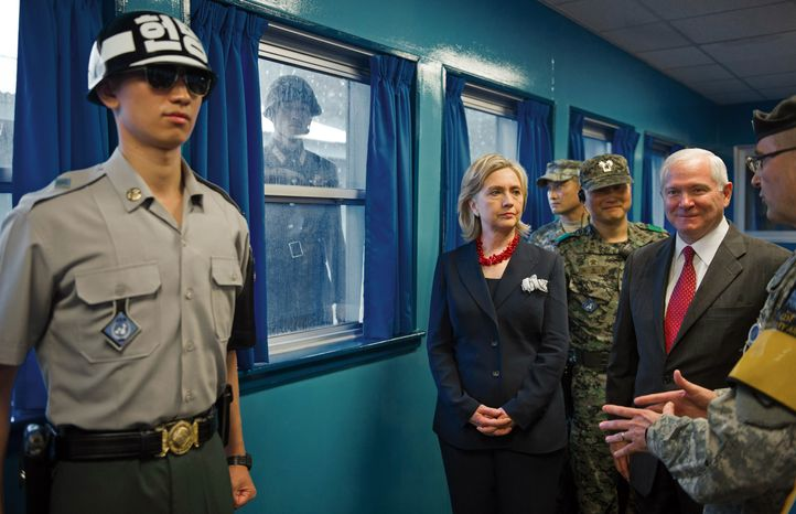 U.S. Army Col. Kurt Taylor, right, briefs Secretary of State Hillary Rodham Clinton, center, and Secretary of Defense Robert Gates, 2nd right,  as a curious North Korean soldier looks through the window at the truce village of Panmunjom in the demilitarized zone that separates the two Koreas since the Korean War, north of Seoul, South Korea, Wednesday, July 21, 2010. (AP Photo/Paul J. Richards, Pool)