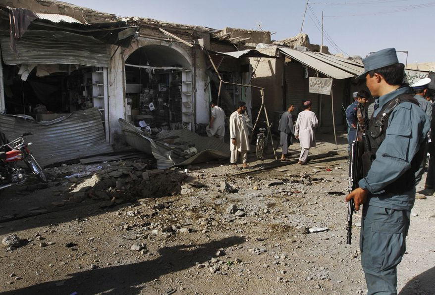 An Afghan policeman stands guard at the site of a suicide bombIng in Kandahar city, south of Kabul, Afghanistan, on Tuesday, July 20, 2010. The explosives were hidden in a cart topped with bottles of juice for sale, Afghan officials. Two civilians were injured in the blast. (AP Photo/Allauddin Khan)
