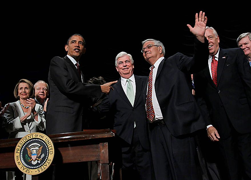 President Barack Obama, left, points to Sen. Chris Dodd, D-Conn., center, and Rep. Barney Frank, D-Mass., right, after signing the Dodd Frank-Wall Street Reform and Consumer Protection Act in a ceremony in the Ronald Reagan Building in Washington, Wednesday, July 21, 2010.(AP Photo/Pablo Martinez Monsivais)