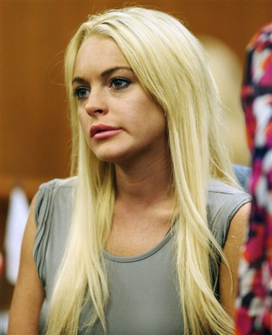FILE - In this Jan. 9, 2011 file photo, actress  Lindsay Lohan is shown at an NBA basketball game between the Los Angeles Laker and the New York Knicks in Los Angeles. Authorities released the 911 call made by Dawn Holland, a Betty Ford Center worker claiming that Lindsay Lohan hit her during a December argument at the facility.  (AP Photo/Alex Gallardo, file)