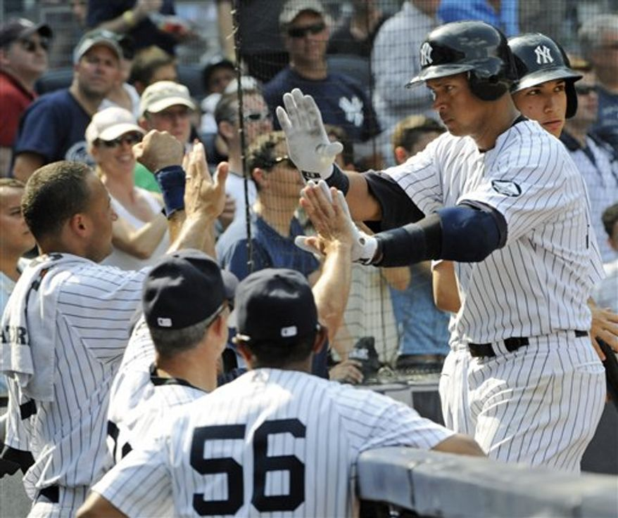 With Tampa Bay Rays' Ben Zobrist, left, at first base, New York Yankees pitcher Phil Hughes, center, winds up in the first inning of a baseball game at Yankee Stadium in New York, Tuesday, Sept. 21, 2010. Yankees first baseman Mark Teixeira is at right. (AP Photo/Kathy Willens)