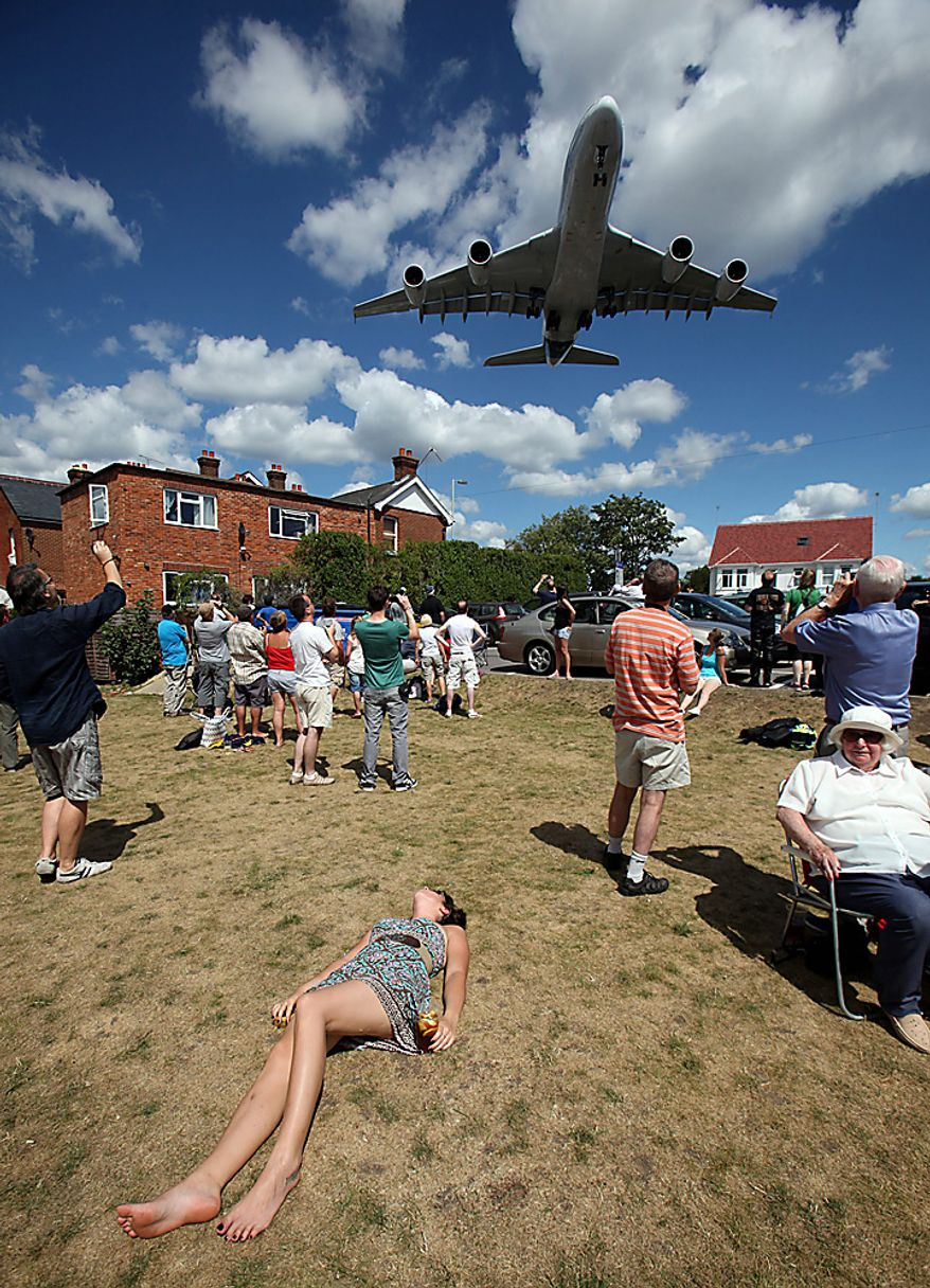 Local residents watch an Airbus SAS A380 airplane fly overhead on the third day of the Farnborough International Airshow in Farnborough, England, on Wednesday, July 21, 2010. The Farnborough International Airshow is being held from July 19-25. Photographer: Simon Dawson/Bloomberg