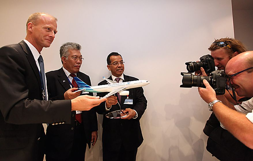 Photographers take a picture of Tom Enders, chief executive officer of Airbus SAS, left, Herry Bakti Gumay, Indonesia's director-general for air transport, second from left, and Emirsyah Satar, chief executive officer of PT Garuda Indonesia Ltd., center, as they pose with a model airplane at a news conference on the third day of the Farnborough International Airshow in Farnborough, England, on Wednesday, July 21, 2010. The Farnborough International Airshow is being held from July 19-25. Photographer: Chris Ratcliffe/Bloomberg