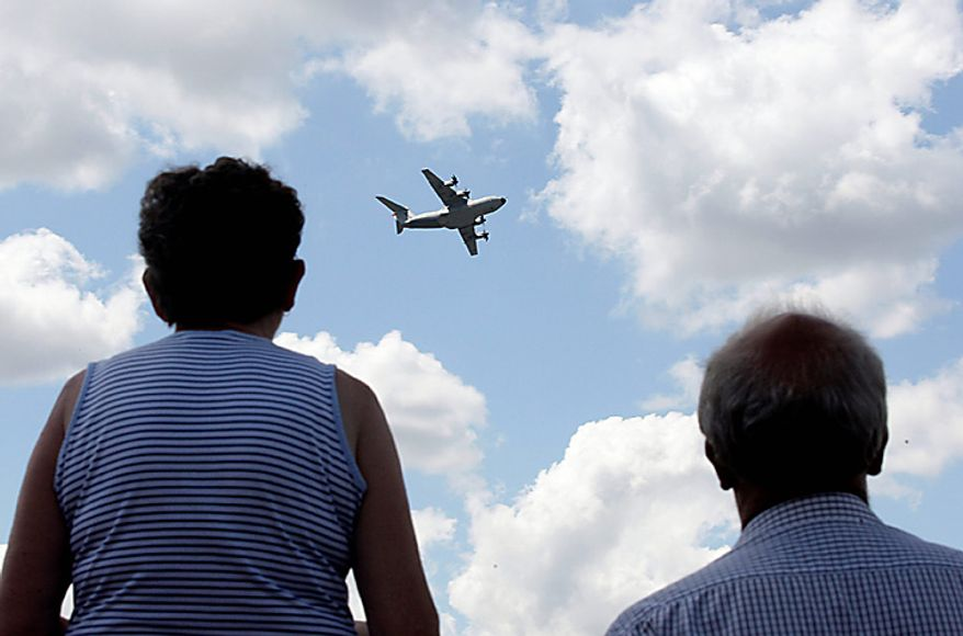 Visitors watch an Airbus SAS A400M military transport plane fly on the third day of the Farnborough International Airshow in Farnborough, England, on Wednesday, July 21, 2010. The Farnborough International Airshow is being held from July 19-25. Photographer: Simon Dawson/Bloomberg