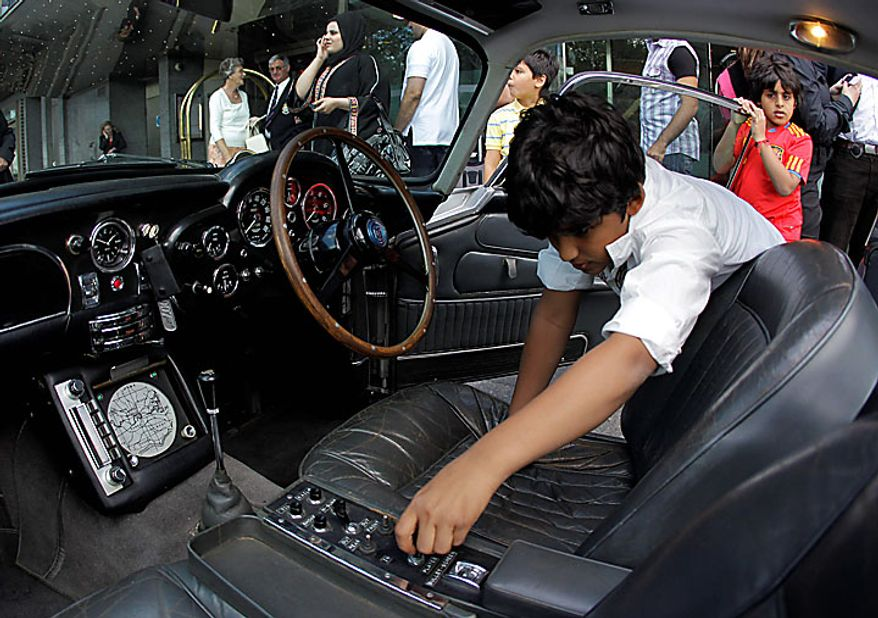 A youngster plays with gadget controls inside the original Aston Martin DB5 car driven by Sean Connery in the James Bond films Goldfinger and Thunderball, as it displayed for the media in London, Wednesday, July 21, 2010.  The car is estimated to fetch in the region of $4.6 million when it is sold at auction in London on Oct. 27.  (AP Photo/Matt Dunham)