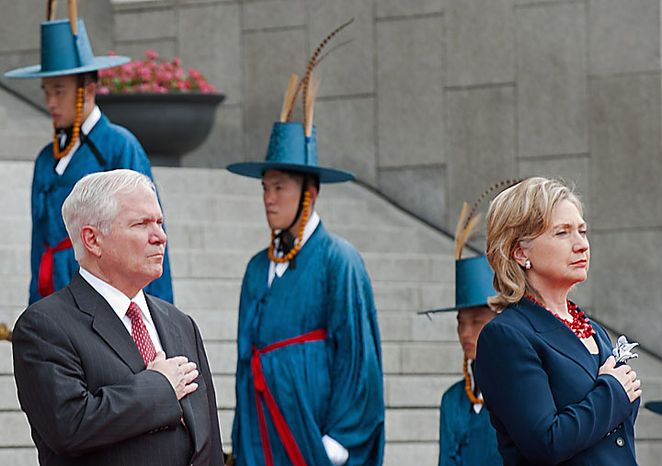 Secretary of Defense Robert Gates, left, and Secretary of State Hillary Rodham Clinton pay respect to the U.S. national anthem during a ceremony at the Korean War Memorial in Seoul, South Korea, on Wednesday, July 21, 2010. (AP Photo/Paul J. Richards, Pool)