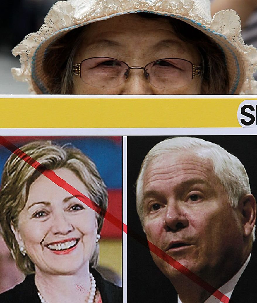A South Korean protester holds a portrait of Secretary of State Hillary Rodham Clinton and Defense Secretary Robert Gates, right, during a rally against joint military exercises by South Korea and the United States in front of the Foreign Ministry in Seoul, South Korea, Wednesday, July 21, 2010. (AP Photo/Lee Jin-man)