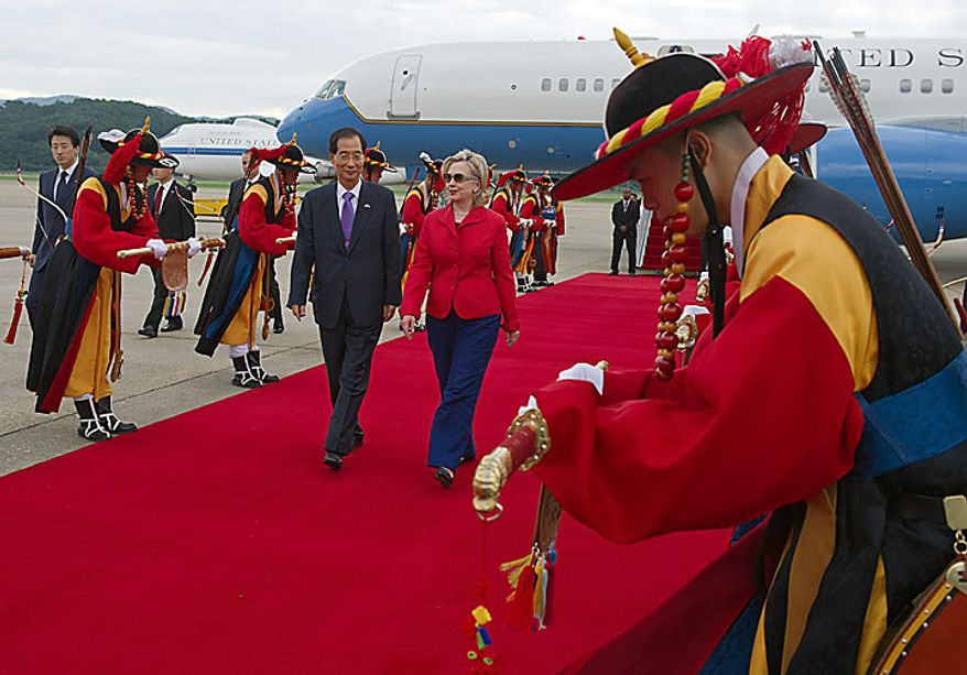 Secretary of State Hillary Rodham Clinton, center right, is escorted by Han Duck-Soo, South Korean ambassador to the U.S., past ceremonial honor guards as she arrives at the Seoul Military Airport in Seongnam, South Korea, Wednesday, July 21, 2010. (AP Photo/Paul J. Richards, Pool)