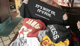 """Sitting in front of a pile of discarded shirts honoring former Cleveland Cavaliers NBA star LeBron James, Yours Truly restaurant manager Christina Weiner holds up the t-shirt that is being exchanged for the turned-in tops at the eatery in Beachwood, Ohio on Tuesday, July 20, 2010.  Organizers of the shirt swap plan to send the discarded shirts to a homeless shelter in James' new city of Miami, and proceeds from the sales of the """"It's Not Us, It's You"""" shirts will go to homeless shelters in Cleveland.  (AP Photo/Amy Sancetta)"""