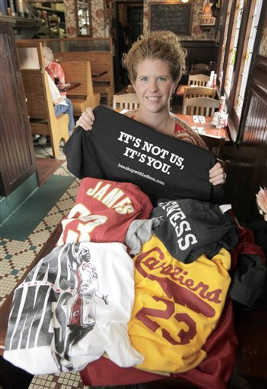 "Sitting in front of a pile of discarded shirts honoring former Cleveland Cavaliers NBA star LeBron James, Yours Truly restaurant manager Christina Weiner holds up the t-shirt that is being exchanged for the turned-in tops at the eatery in Beachwood, Ohio on Tuesday, July 20, 2010.  Organizers of the shirt swap plan to send the discarded shirts to a homeless shelter in James' new city of Miami, and proceeds from the sales of the ""It's Not Us, It's You"" shirts will go to homeless shelters in Cleveland.  (AP Photo/Amy Sancetta)"