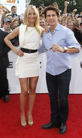 US actors Tom Cruise und Cameron Diaz, left, smile as they pose on the red carpet to promote the film 'Knight and Day' in Munich, Germany Wednesday July 21, 2010. (AP Photo/ddp/Timm Schamberger)