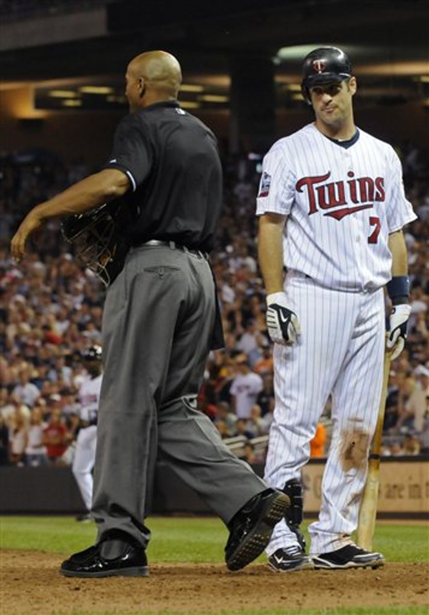 Minnesota Twins' Joe Mauer, right, looks at plate umpire C.B. Bucknor after he was called out looking against the Cleveland Indians in the sixth inning of a major league baseball game Monday, July 19, 2010 in Minneapolis. The Indians won 10-4. (AP Photo/Jim Mone)
