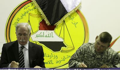 Iraq's Minister of Justice Dara Noureddin, left, and U.S. Army Maj. Gen. Jerry Cannon, right, sign documents handing the U.S. Theater Internment Facility at Camp Cropper to Iraqi control at a ceremony, Thursday, July 15, 2010 in Baghdad. (AP Photo/Maya Alleruzzo)