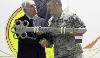 In this Thursday, July 15, 2010, file photo, Iraq's Minister of Justice Dara Noureddin, left, and U.S. Army Maj. Gen. Jerry Cannon, right, hold a symbolic key to the U.S. Theater Internment Facility at Camp Cropper during a ceremony transferring the facility to Iraqi control in Baghdad, Iraq. Iraq's justice minister says four al Qaeda-linked detainees have escaped from the Baghdad area prison that was handed over by the U.S. to Iraqi authorities a week ago. (AP Photo / Maya Alleruzzo, File)