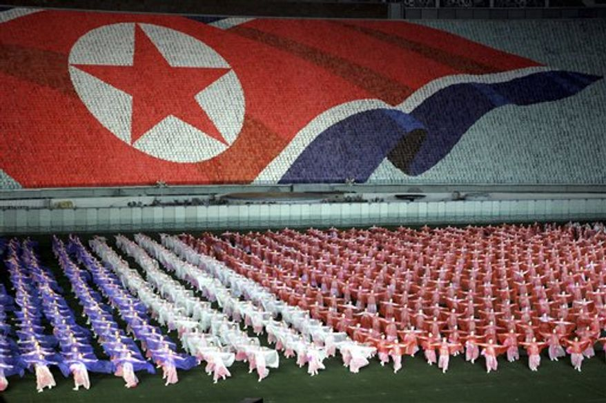 "FILE - In this Oct. 11, 2005 file photo, North Koreans perform with scarves showing the colors of the North Korean flag near an image of the flag formed by tens of thousands of children holding up colored cards during the annual massive propaganda spectacle known as a ""mass game"" held in Pyongyang, North Korea. North Korea said Thursday, July 22, 2010 it will stage massive propaganda spectacles next month amid lingering tensions over the deadly sinking of a South Korean warship blamed on Pyongyang. (AP Photo/Ng Han Guan, File)"