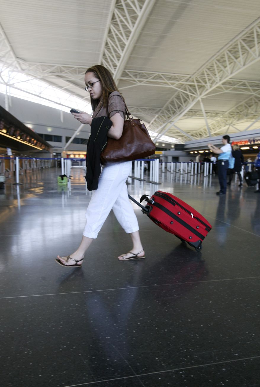 ** FILE ** In this May 21, 2008 file photo, a passenger pulls he carry-on suitcase through the American Airlines terminal at John F. Kennedy Airport in New York. Carrying your bag onto the plane yourself means you'll skip more than just the airport's baggage claim these days. (AP Photo/Mark Lennihan)