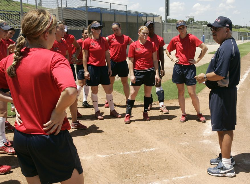 Coach Jay Miller, right, talks with his players at the start of a U.S. national softball team practice in Oklahoma City, Tuesday, July 20, 2010. The World Cup of Softball takes place this week. (AP Photo/Sue Ogrocki)