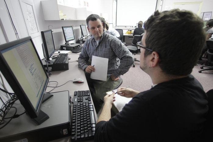 Eric Bilderback (left) holds his resume as he talks with Mike Watson, a business employment specialist at WorkSource Oregon, on Tuesday, July 20, 2010, in Portland, Ore. Congress approved a
