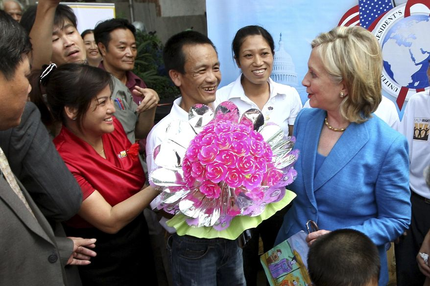 A man presents flowers to Secretary of State Hillary Rodham Clinton, right, after she signed a memorandum of understanding for U.S. support of HIV/AIDS programs in Vietnam, at Ngoc Lam Pagoda in Hanoi, Vietnam, on Thursday July, 22, 2010. (AP Photo/Julian Abram Wainwright, Pool)