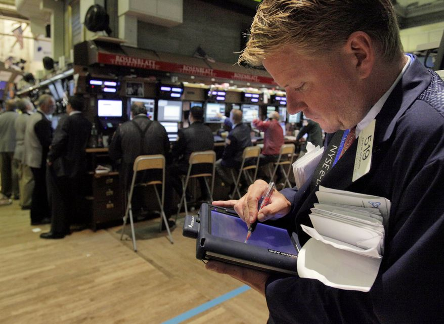 In this July 21, 2010, photo, trader John Bowers uses his handheld device as he works on the floor of the New York Stock Exchange. Stock futures are barely off their highs of the morning after the government says weekly jobless claims jumped more than expected last week. (AP Photo/Richard Drew)