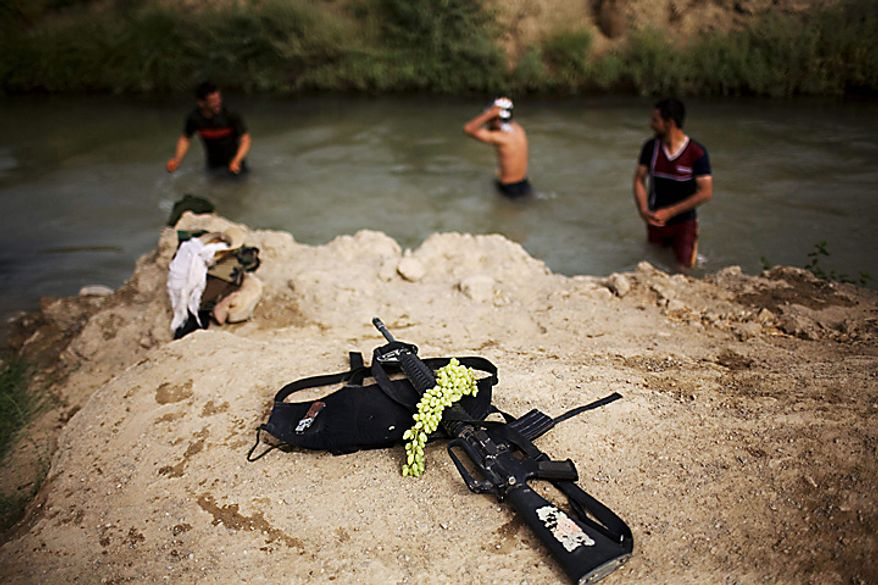 Afghan army soldiers leave grapes and a weapon aside as they cool off from the fierce heat with a swim in a canal near the joint Afghan-U.S. base COP Nolen, in the volatile Arghandab Valley, Kandahar, Afghanistan, Thursday, July 22, 2010. (AP Photo/Rodrigo Abd)