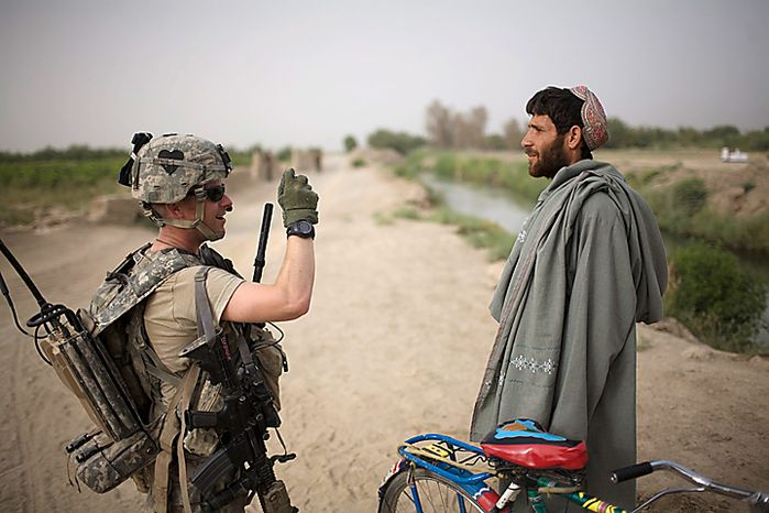 U.S. Army 1st Lt. Christopher Babcock, from New Orleans, La., photographs an Afghan villager for intelligence purposes after he was stopped cycling near COP Nolen, in the volatile Arghandab Valley, Kandahar, Afghanistan, Thursday, July 22, 2010.