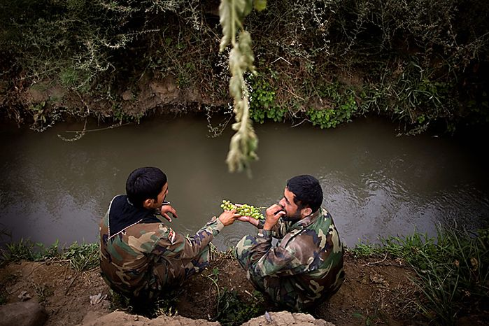 Afghan army soldiers share grapes beside a small canal after arriving to reinforce U.S. troops at Combat Outpost Nolen, in the volatile Arghandab Valley, in Kandahar, Afghanistan, Thursday, July 22, 2010. (AP Photo/Rodrigo Abd)