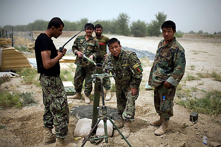 Afghan army soldiers prepare to fire a 60 mm mortar on insurgent positions in a village near Combat Outpost Nolen, in the volatile Arghandab Valley, in Kandahar, Afghanistan, Thursday, July 22, 2010. (AP Photo/Rodrigo Abd)
